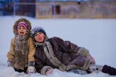 Roliga barn som spelar och skrattar på snöig vinter Royaltyfri Bild
