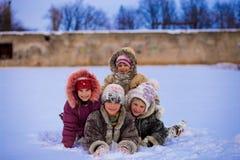 Roliga barn som spelar och skrattar på snöig vinter Arkivbilder