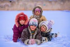 Roliga barn som spelar och skrattar på snöig vinter Royaltyfri Foto