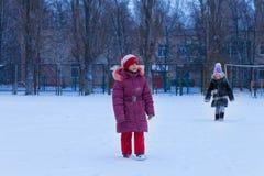 Roliga barn som spelar på snöig vinter Arkivfoton