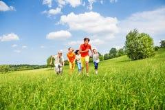 Roliga barn som tillsammans kör i fältet Royaltyfria Bilder