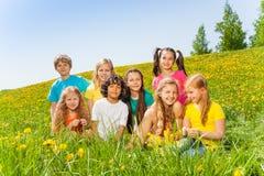 Roliga barn som tillsammans sitter på grönt gräs Royaltyfri Foto