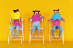 Roliga barnflickor läste böcker på kulör gul bakgrund royaltyfria foton