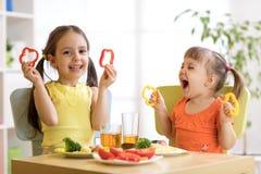 Roliga barnflickor som äter sund mat Ungar äter lunch hemma eller dagiset arkivfoton
