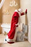 Roliga berusade Santa Claus som peeing i toaletten Fotografering för Bildbyråer