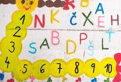 Roliga bokstäver och nummer på väggen Arkivbild