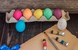 Roliga easter ägg med målning borstar på gammalt papper Ordna till till PA Arkivbild