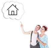 Roliga familjpar som omfamnar och pekar på dröm- hus Arkivfoton
