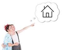 Roliga familjpar som omfamnar och pekar på dröm- hus Arkivfoto