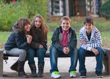 roliga flickor för pojkar som har den tonårs- parken Royaltyfri Foto