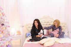 Roliga flickor kommer av till mest full på säng för kall musik på smartph Royaltyfria Foton