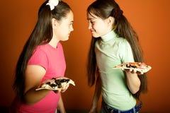 roliga flickor mitt emot pizza Arkivbilder