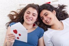 roliga flickor som har bokstavsförälskelseavläsning tillsammans Royaltyfri Bild
