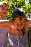 roliga flickor som har vatten Arkivbilder