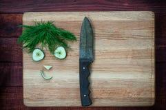 Roliga framsidor av gurkaskivor och dill på skärbrädawina Royaltyfria Bilder