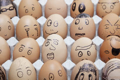 Roliga framsidor målade på på bruna ägg som var ordnade i låda Arkivbilder