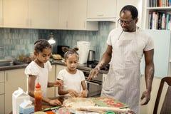 Roliga gulliga flickor som har deras framsidor i mjöl, medan göra pizza royaltyfria foton