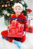 Roliga iklädda röda nattpyjamas för liten unge och hatt av santa Royaltyfri Foto