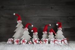 Roliga julträd med santa hattar och gåvaaskar på träb Arkivbilder