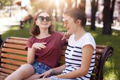 Roliga kvinnliga tonåringar skrattar joyfully, medan berätta sig roliga berättelser, iklädd tillfällig kläder, sitter på träbänk  Fotografering för Bildbyråer