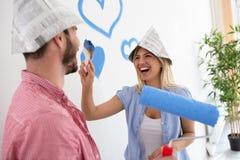 Roliga le par som målar det nya hemmet Royaltyfri Bild