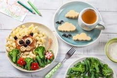 Roliga Lion Food Face med kotletten, pasta och grönsaker Arkivfoton