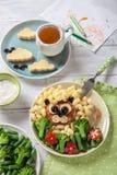 Roliga Lion Food Face med kotletten, pasta och grönsaker Arkivbild
