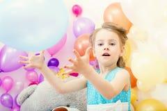 Roliga liten flickalekar med ballongen i studio Royaltyfri Fotografi
