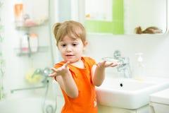 Roliga liten flickatvagninghänder i badrum Arkivfoto