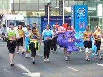Roliga löpare på den London maratonen 22. April 2012 Arkivbild