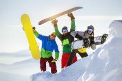 Roliga lyckliga snowboarders för grupp tre fotografering för bildbyråer