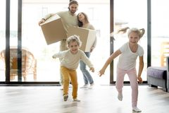 Roliga lyckliga ungar som kör in i nytt hus på rörande dag arkivfoton