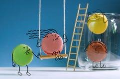 Roliga macarons har en bra tid bredvid kruset för sötsaker Royaltyfria Bilder