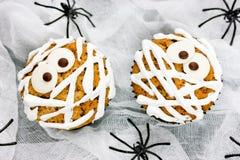 Roliga mammamuffin på vit bakgrund med spindlar Arkivfoto