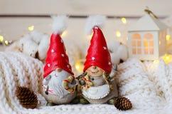 Roliga par av julgnomer i röda lock Arkivbilder