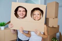 Roliga par med en ask på huvudet i ett nytt hus Royaltyfria Foton