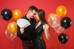 Roliga par som firar pengar för kassa för lott för håll för födelsedagferieparti, kreditkort som isoleras på ljus röd bakgrundslu royaltyfri fotografi