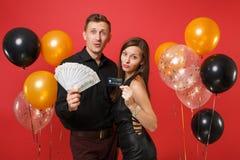 Roliga par som firar pengar för kassa för lott för håll för födelsedagferieparti, kreditkort som isoleras på ljus röd bakgrundslu royaltyfri foto