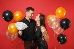 Roliga par som firar pengar för kassa för lott för håll för födelsedagferieparti, kreditkort på ljus röd bakgrundsluft royaltyfri foto