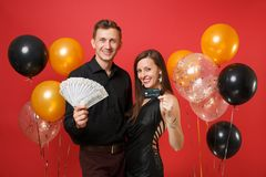 Roliga par som firar pengar för kassa för lott för håll för födelsedagferieparti, kreditkort på ljus röd bakgrundsluft arkivbilder