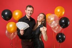 Roliga par som firar pengar för kassa för lott för håll för födelsedagferieparti, kreditkort på ljus röd bakgrundsluft royaltyfri bild