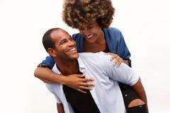 Roliga par som ler i omfamning vid den vita väggen arkivfoton