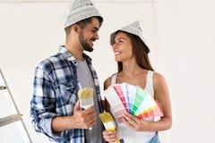 Roliga par som väljer färger för att måla deras nya hus Arkivbild