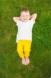 Roliga pojken som den har, solbadar att ligga på gräset Royaltyfri Fotografi