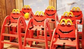 Roliga röda barns stolar i ett kafé royaltyfri fotografi