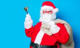 Roliga Santa Claus har en gyckel med klockan Royaltyfri Foto