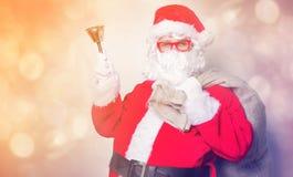 Roliga Santa Claus har en gyckel med klockan Arkivbild