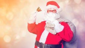 Roliga Santa Claus har en gyckel med klockan Royaltyfria Foton