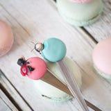 Roliga skedar med macarons och nyckelpigor Arkivfoton
