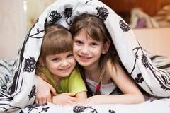 Roliga skinn för små systrar under en filt Arkivbilder